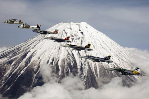 Seven US Navy aircraft, embarked aboard the USS Kitty Hawk, fly past Mount Fuji in Japan. From left they are an E-2, C-2, EA-6, two F/A-18 Super Hornets and two F/A-18 Hornets. (DoD)