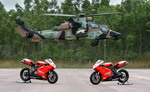 An Australian Army Tiger hovers over two Ducatis from the Australian Ducati Super Bike team on 7 April 2010. (Australian DoD)